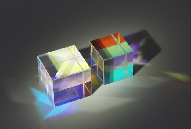 Dwa szklane pryzmaty sześcienne załamują światło na różne kolory i rzucają cienie