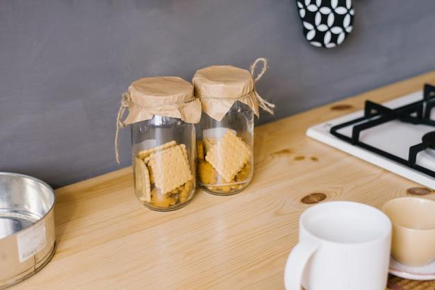 Dwa szklane słoiki domowych ciasteczek na drewnianym blacie w kuchni