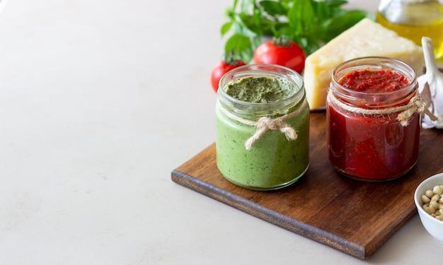 Dwa szklane słoiki z czerwonym pesto i pesto bazyliowym. kuchnia narodowa. zdrowe odżywianie. jedzenie wegetariańskie.