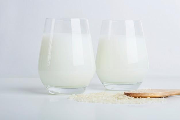 Dwa szklanki wegańskiego mleka ryżowego i ziaren ryżu na białym tle