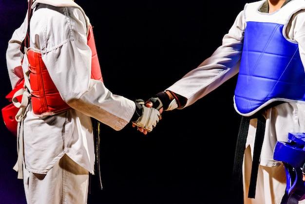 Dwa taekwondo to uścisk dłoni. przed meczem na białym tle