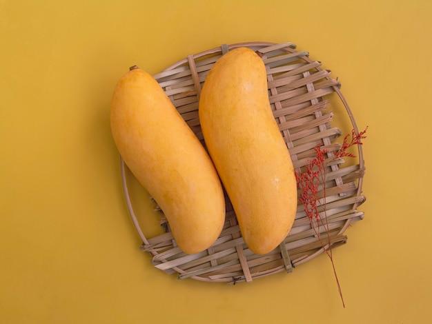Dwa tajskie mango z żółtą skórką i suszonym kwiatem na plecionej tacy