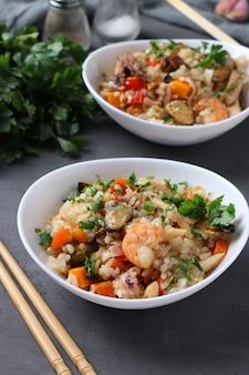 Dwa talerze smażony ryż z owocami morza, warzywami, imbirem i pietruszką na ciemnym tle. kuchnia azjatycka. jedzenie wegetariańskie. format pionowy. zbliżenie