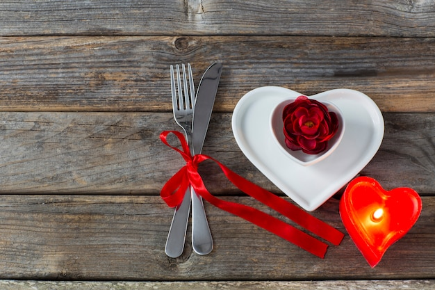 Dwa talerze w kształcie serca, czerwony pąk róży, czerwona świeca w kształcie serca i sztućce związane czerwoną wstążką