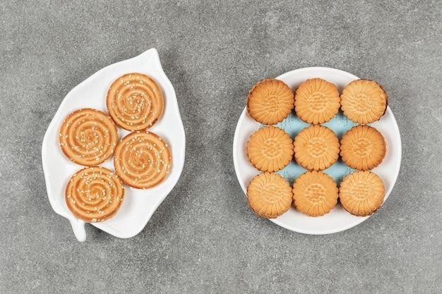 Dwa talerze z ciasteczkami kanapkowymi i herbatnikami z sezamem