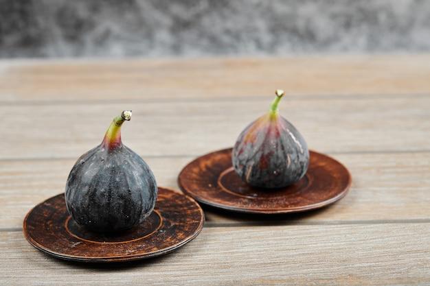 Dwa talerze z figami na drewnianym stole.