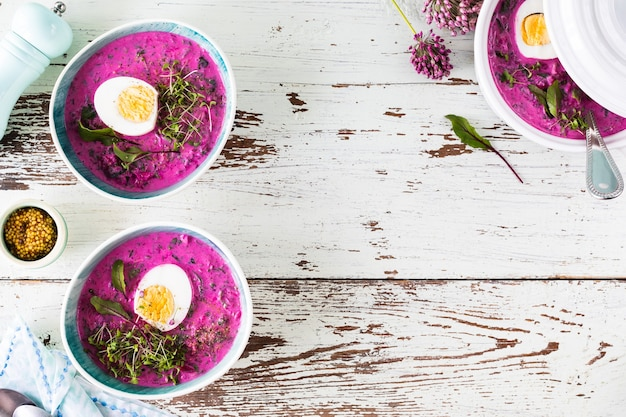 Dwa talerze zimnej letniej zupy z buraków, ogórków i jajek na drewnianym stole. widok z góry. skopiuj miejsce.