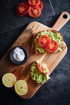Dwa tosty z awokado i pomidorami z solą i cytryną na desce do krojenia