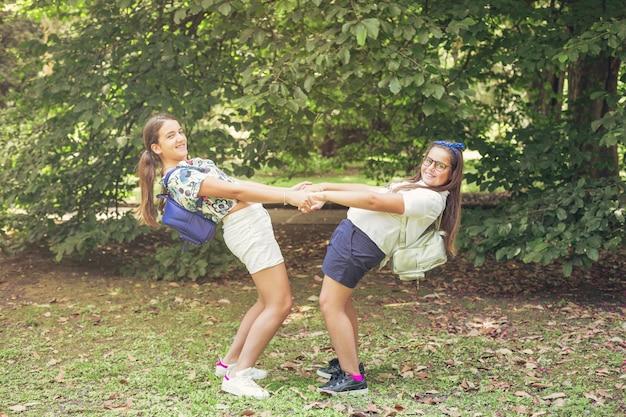 Dwa uczennicy bawić się wpólnie w lasu parku