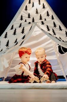 Dwa urocze małe kaukaski dzieci chłopiec i piękna dziewczyna w kratkę czerwone ubrania