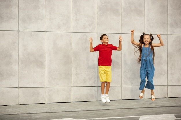 Dwa uśmiechnięte dzieci, chłopiec i dziewczynka razem biegają w mieście, miasto w letni dzień