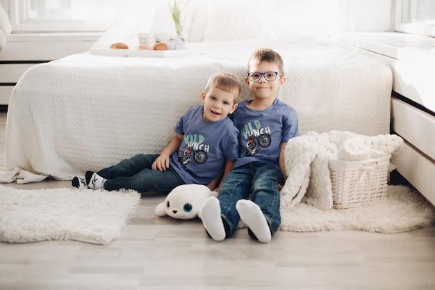 Dwa uśmiechnięte dziecko płci męskiej pozowanie razem w wygodnej białej sypialni wnętrza. szczęśliwi bracia przytulają się, bawiąc się w przytulnym domu, siedząc na podłodze w pobliżu łóżka