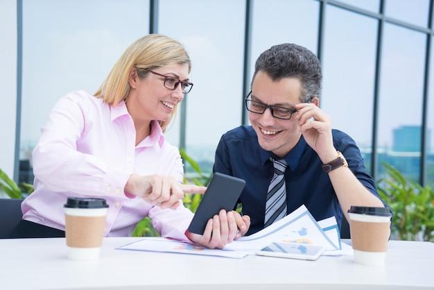 Dwa uśmiechniętego biznesowego kolegi używa telefon przy kawiarnią na przerwie.