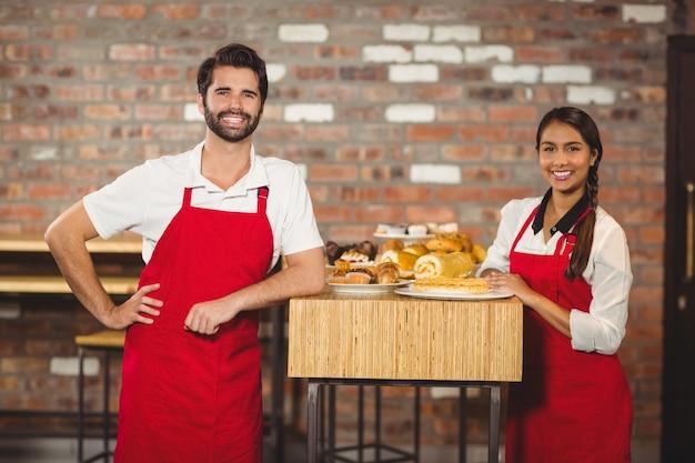 Dwa uśmiechniętego kelnera patrzeje kamerę