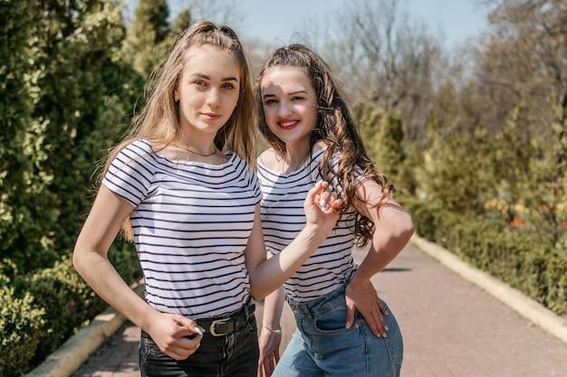 Dwa uśmiechniętego młodego żeńskiego dziewczyna przyjaciela ma zabawę w parku
