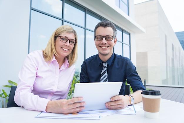 Dwa uśmiechniętego partnera biznesowego używa pastylkę przy plenerową kawiarnią.