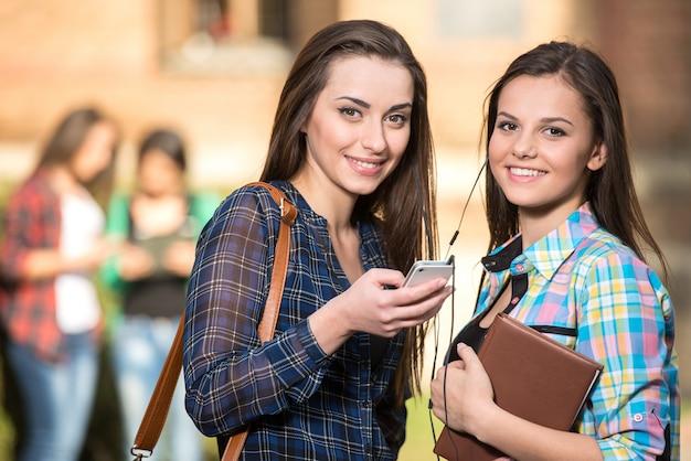 Dwa uśmiechniętego żeńskiego ucznia przy szkołą wyższa.