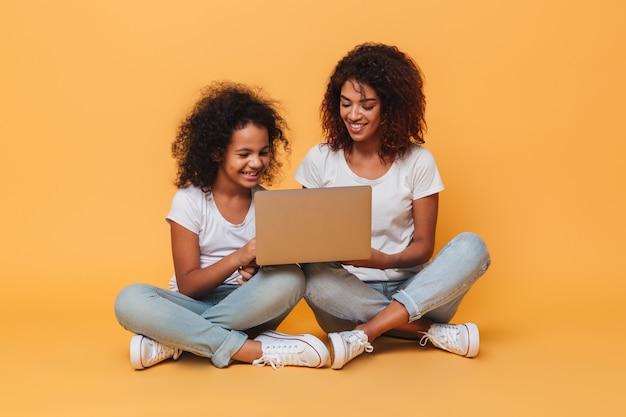 Dwa uśmiechniętej afro amerykańskiej siostry używa laptop podczas gdy siedzący