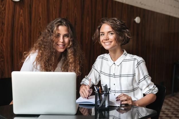 Dwa uśmiechniętej kędzierzawej kobiety pracuje stołem