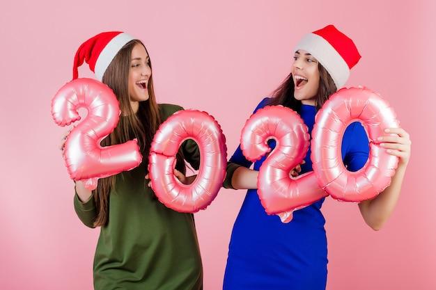 Dwa uśmiechniętej kobiety jest ubranym santa kapelusze trzyma 2020 balonów dla nowego roku wakacje odizolowywających nad menchiami
