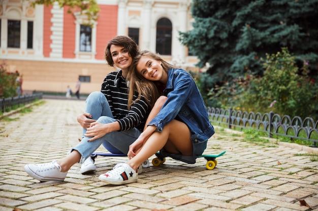 Dwa uśmiechniętej młodej nastoletniej dziewczyny siedzi wpólnie