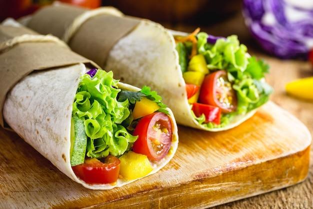 Dwa wegetariańskie zawijane tortille na drewnianej desce do krojenia z warzywami na powierzchni
