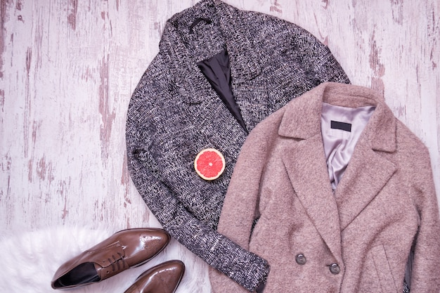 Dwa wełniany płaszcz, brązowe lakierowane buty na białym futrze, pół grejpfruta, drewniane tło. koncepcja mody. widok z góry