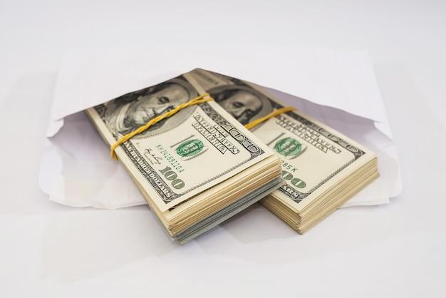 Dwa wiązki dolarów przewiązane gumką w białej kopercie. dużo pieniędzy.