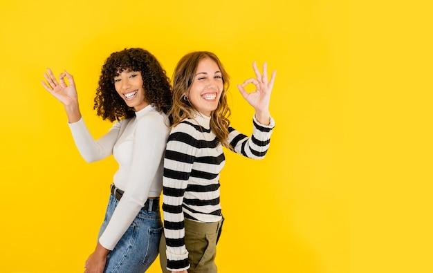 Dwa wielorasowe młode piękne modelki pozujące z ok gestem uśmiechnięte na białym tle