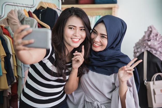 Dwa właściciel sklepu mody biorąc selfie razem