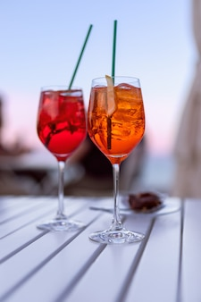 Dwa włoskie aperitify nad morzem o zachodzie słońca (zdjęcie w pionie)