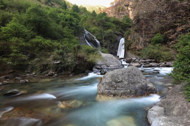 Dwa wodospady w małej spokojnej dolinie z jasną turkusową wodą przepływającą między dużymi kamieniami