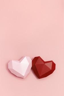 Dwa wolumetryczne papierowe serca w kolorze czerwonym i różowym