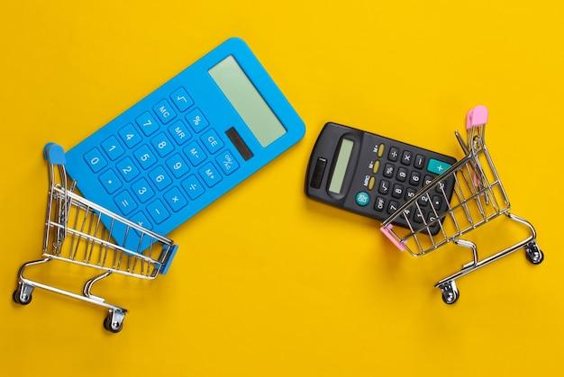 Dwa wózki mini supermarketów z żółtymi kalkulatorami