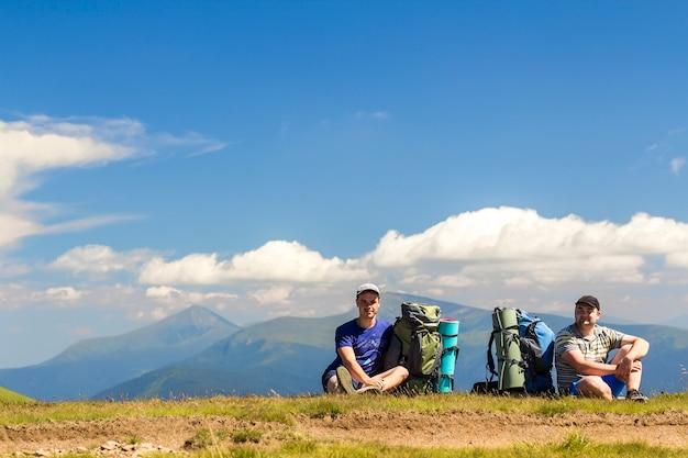 Dwa wycieczkowicza siedzi na wzgórzu z górami w widoku z plecakami
