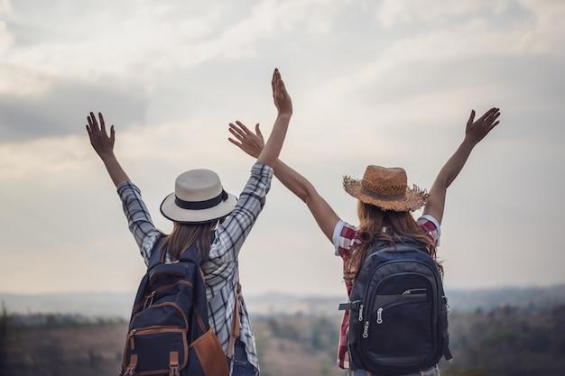 Dwa wycieczkowicza stoi w górach z powstającymi rękami przy niebem