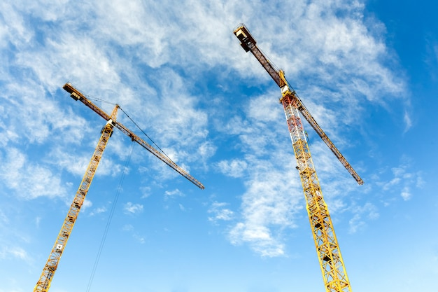 Dwa wysokie żurawie wieżowe pracują nad budową nowych domów. szeroki kąt.