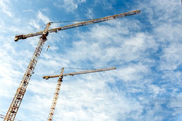Dwa wysokie żurawie wieżowe pracują przy budowie nowych domów