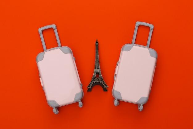 Dwa zabawkowe walizki podróżne, figurka wieży eiffla na pomarańczowo. planowanie podróży