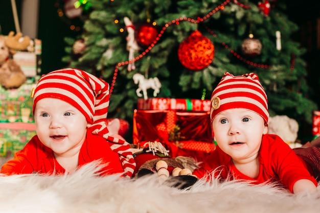 Dwa zabawne bliźniaki w czerwonych garniturach leżą przed bogatą choinką