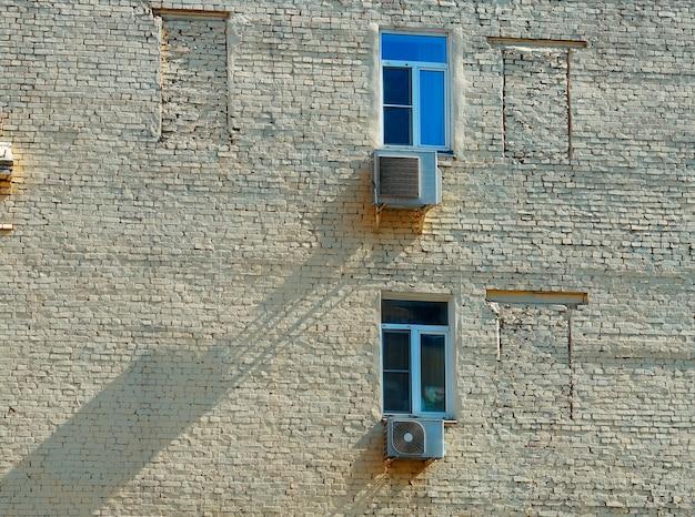 Dwa zamknięte okna w tle ceglanego budynku