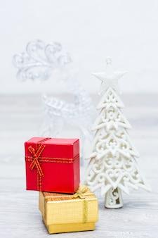 Dwa zapakowane prezenty w pudełkach, choinki i jelenia na szarym tle drewnianych