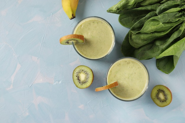 Dwa zdrowe smoothie detox kiwi, banan, szpinak w okularach na jasnoniebieskim tle ze świeżymi składnikami