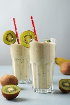 Dwa zdrowe smoothie detox kiwi i banan w wysokich szklankach na jasnoniebieskim tle ze świeżymi składnikami