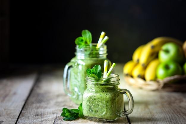 Dwa zdrowe zielone koktajle ze szpinakiem, bananem, jabłkiem i miętą w szklanym słoju i składnikach. detox, dieta, zdrowe, wegetariańskie jedzenie koncepcja. skopiuj miejsce