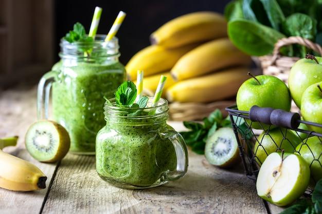 Dwa zdrowe zielone koktajle ze szpinakiem, bananem, jabłkiem, kiwi i miętą w szklanym słoju i składnikach. detox, dieta, zdrowe, wegetariańskie jedzenie koncepcja.