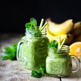 Dwa zdrowe zielone koktajle ze szpinakiem, bananem, pomarańczą i miętą w szklanym słoju i dodatkach. detox, dieta, koncepcja zdrowej, wegetariańskiej żywności.