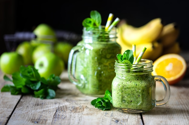 Dwa zdrowe zielone koktajle ze szpinakiem, bananem, pomarańczą, jabłkiem, kiwi i miętą w szklanym słoiku i składnikach. detox, dieta, koncepcja zdrowej, wegetariańskiej żywności.
