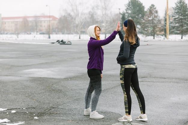Dwa żeńska biegacz pozycja na ulicie daje wysokości pięć
