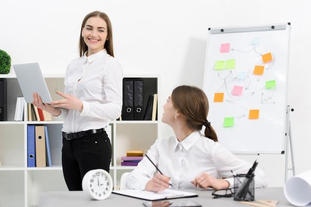 Dwa żeński kolega patrzeje each inny podczas gdy pracujący w biurze